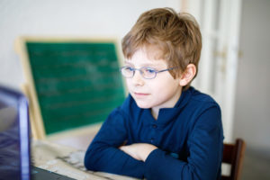 Glasses for young children help this boy see his the computer screen
